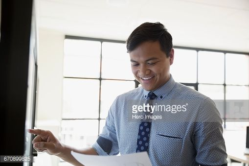 Stock Photo : Smiling businessman with paperwork using touch screen television in conference room