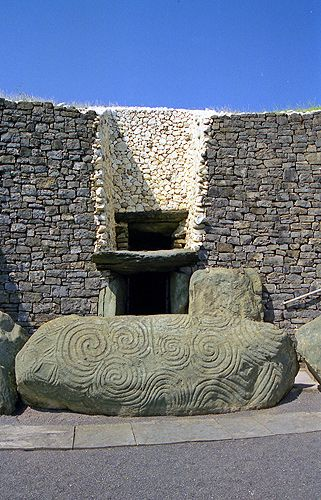 Newgrange is a prehistoric monument, part of the complex of Megalithic sites of Brú na Bóinne in Ireland. Shown is the retaining wall at the front. The sides and back are ringed by 'kerbstones' engraved with artwork. (35th-32nd centuries BC)