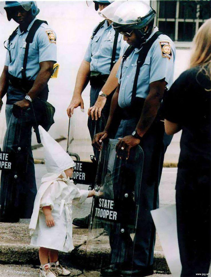 Ребенок члена организации Ку–клукс–клан, играющий со своим отражением на щите полицейского во время демонстрации, 1992 год, Джорджия, США — Фотографии из прошлого