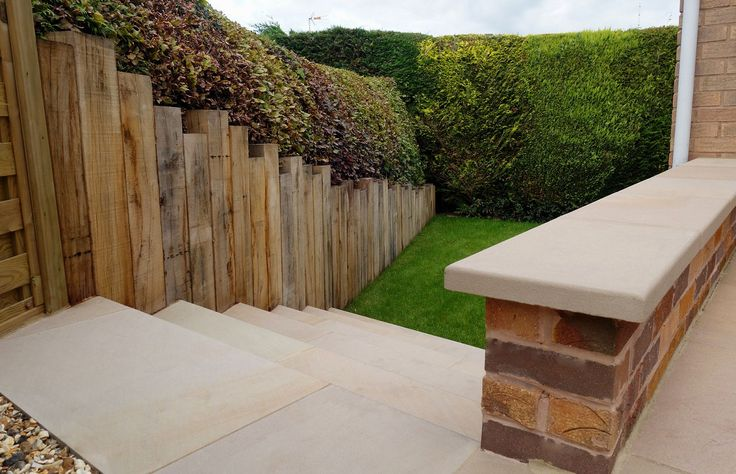 After Redesign & Landscaping - top of steps - retaining brick wall with sawn sandstone coping now acts as an extra seat. Sawn sandstone paving, bull nose steps, vertical oak sleeper wall, low maintenance garden, contemporary garden