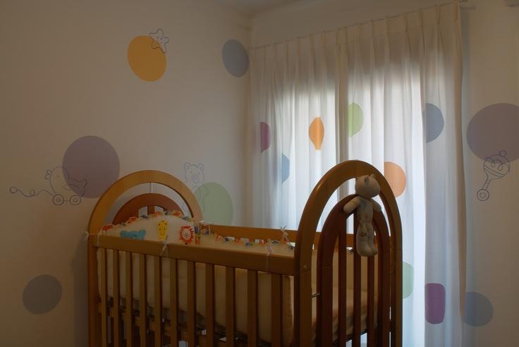 O detalhe da cortina passou para a pintura especial das paredes neste dormitório de bebê