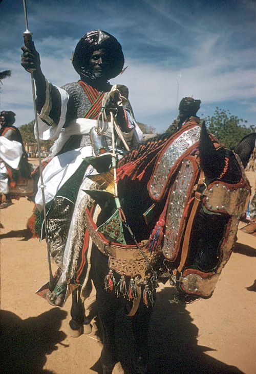 Mounted armed guards of the Emir of Katsina during the festival of Sallah, Katsina, Nigeria.  The festivals of Sallah are celebrated on the two big Muslim holidays, Eid-el-Fitri and Eid-el-kabir, in December and February. The Emir's armed guards are dressed in the manner of ancient soldiers. Vests of chain armor are visible under the swirling blue robes, and faces peer out from dark indigo turbans wrapped around the head and under the chin, 1959.