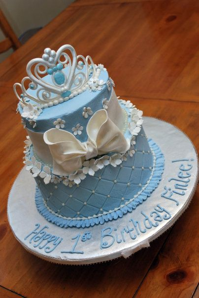 Princess Cake - Request for princess cake- the little girl's favorite was cinderella, but liked all the princesses so went with blue. Gumpaste tiara painted with pearl dust, fondant bow, ribbon and flowers. Diamond impression mat on bottom tier, sugar pearls, ruffle border topped with tiny bead border both from buttercream.