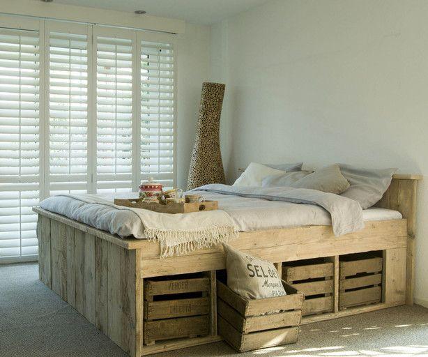 Een mooi bed van steigerhout met daarin fruitkistjes als opbergruimte