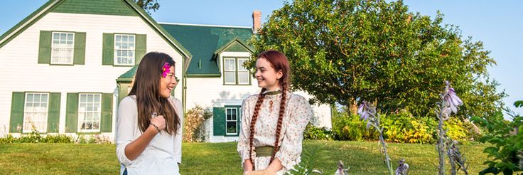 Anne impersonator sits laughing with a visitor outside of Green Gables.