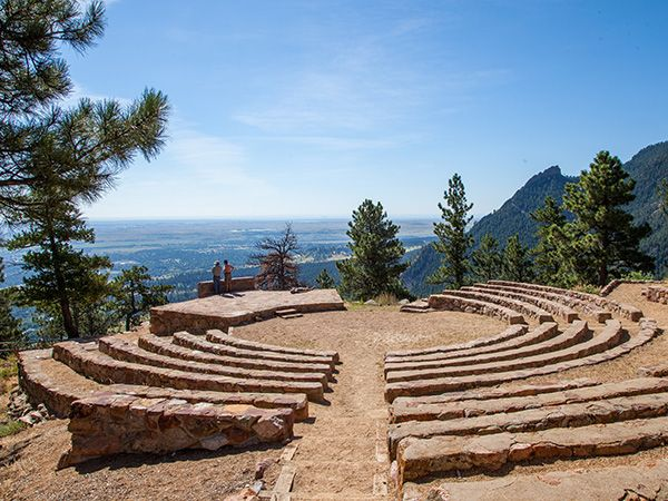 Sunrise Circle Amphitheater, Boulder, CO | Located in a naturally occurring, acoustically sound depression in a cliff overlooking the City of Boulder, this open-air theater is one of 3 structures on Flagstaff Mountain built by the Civilian Conservation Corps. Completed in 1934 and providing seating for 150 people, Sunrise Circle Amphitheater is comprised of twelve rows of semi-circular stone benches facing east to an elevated stone stage…