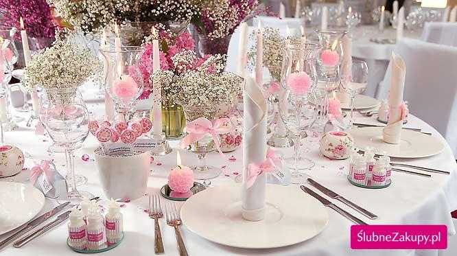 lizaki z bilecikami podziekowania dla gości, różowa kokardka, szklany świecznik, biała świeca prosta, różowe świeczki, świecznik szklany niski, kryształki różowe, obrus biały okrągły, okrągła podstawka pod świecznik lustro, serwetka biała