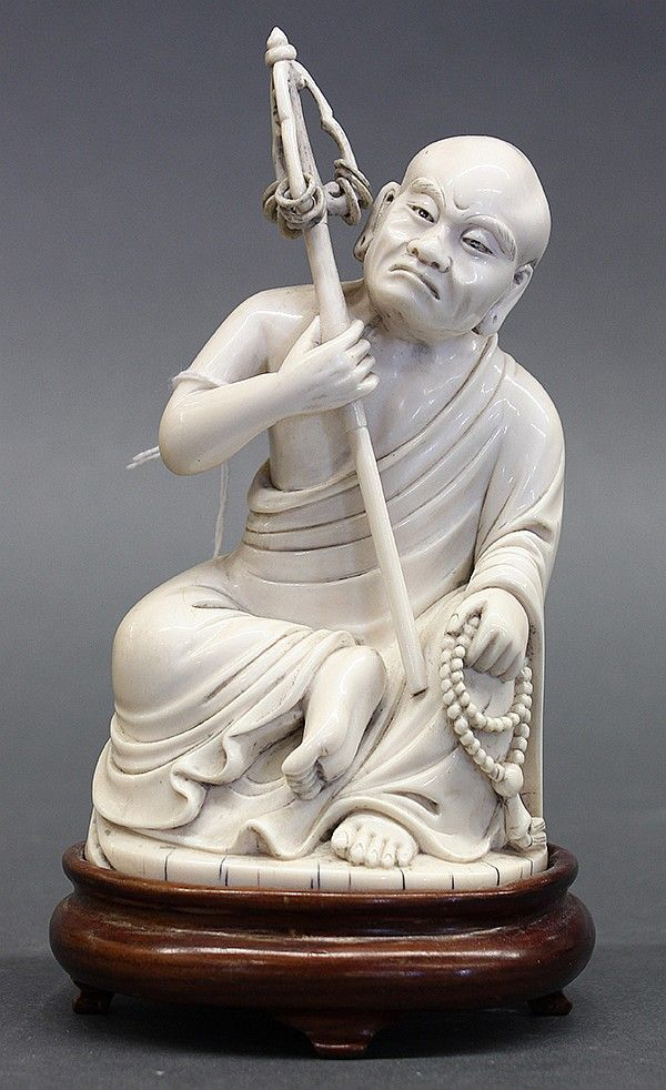 """Chinese ivory figural carving, late Qing/early Republic period, of a luohan seated in royal ease holding a staff and a strand of prayer beads, with wood stand, ivory: 5.75""""h"""