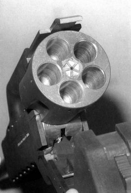 A close-up view of the gun's cylinder area. The cartridge extractor, in the center, was actuated by the curved lever within the carry handle.