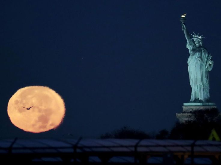 The supermoon appears near the Statue of Liberty, Monday, Nov. 14, 2016, in New York. Monday's supermoon, a phenomenon that happens when the moon makes a close pass at the earth, is the closest to earth since 1948. Picture: AP Photo/Julio Cortez