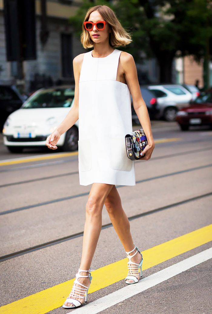 A white shift dress with pockets is worn with white strappy sandals, a colorful clutch, and red sunglasses