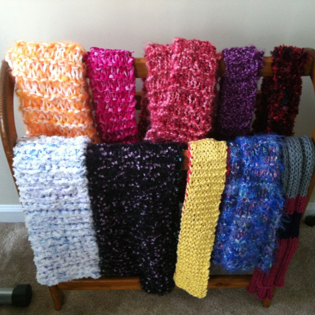 Some of my hand knit scarfs displayed on a quilt rack