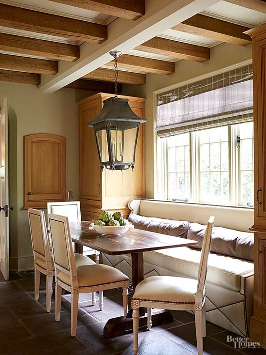 Perfect for a combined living/dining room, this banquette features a built-in box covered with throw pillows. Low back cushions don't block the window but offer a bit of extra comfort. A large table can accommodate four more chairs when needed./