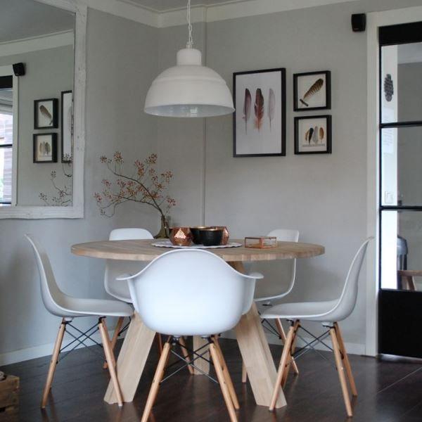 Een ronde tafel zorgt voor een knusse eethoek. De stoelen die je hier ziet zijn de klassieke Vitra Eames DSW stoel (zonder armleuning) en de Vitra Eames DAW stoel (met armleuning).