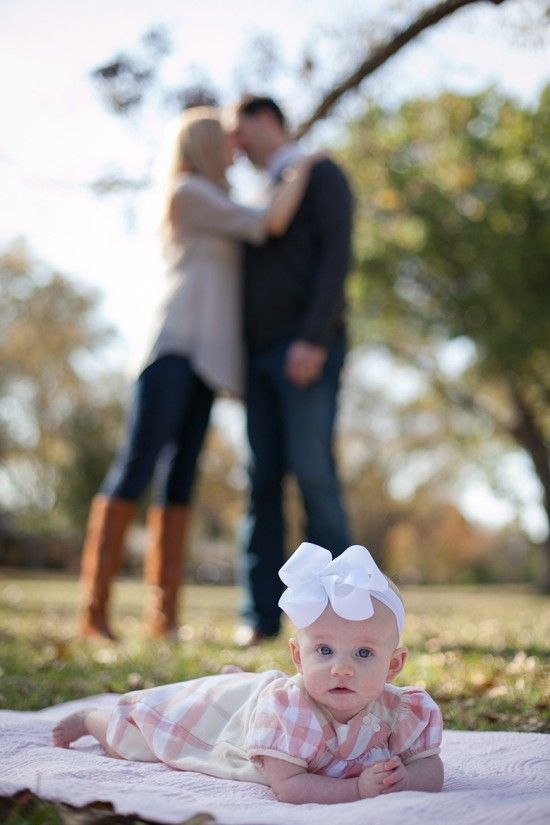 Baby girl with parents kissing in background   View La La Photography