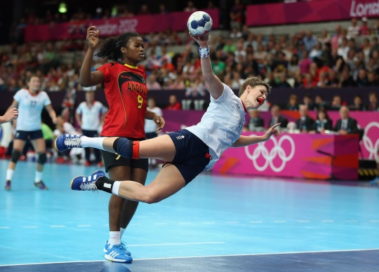 Lyn Byl #11 of Great Britain shoots past Isabel Guialo #9 of Angola in Women's Handball match.