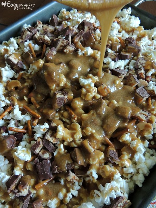 Preparing Sweet & Salty SNICKERS Popcorn 3 regular sized bags of Lightly Salted Microwave Popcorn, popped and kernels removed 1/2 cup unsalted butter 1/2 cup light corn syrup 2 cups brown sugar 1/2 tsp. salt 1/2 tsp. baking soda 1/2 tsp, vanilla extract 6 Snickers candy bars, regular size, chopped 1 cup salted pretzel sticks broken up into smaller pieces 3/4 cup mixed nuts