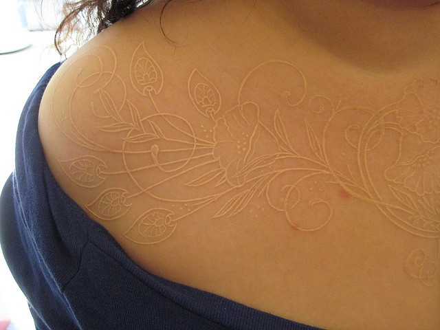 white flower tattoo (i THINK this is white ink and not scarification...)