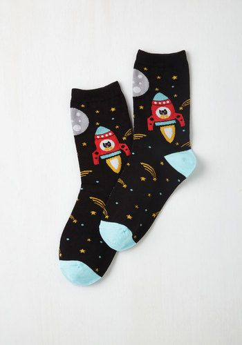 Get 'whiskered' away by adorable fashions with these patterned crew socks! A cosmic display of shooting stars, red spaceships, and feline space explorers fly about this black and aqua pair for out-of-this-world outfits!