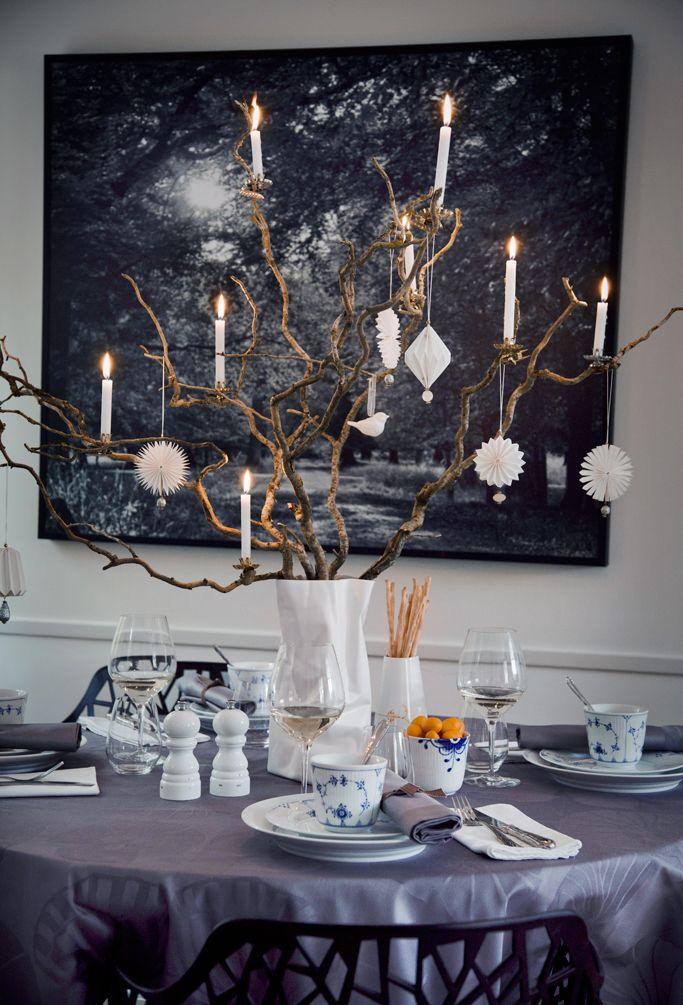 Dæk julebordet med et moderne twist i grå og violette nuancer. Brug sæsonens smukke, hvide julekugler, fugle, ugler og stjerner. Brug de smukkeste porcelæn, stentøj og pynt med troldegrene og levende lys. Det giver på en gang råhed, hygge og moderne elegance.Stellet på bordet er en kombination af Royal Copenhagen Musselmalet Riflet, Blue Elements, Mega Mussel, Hvidriflet.
