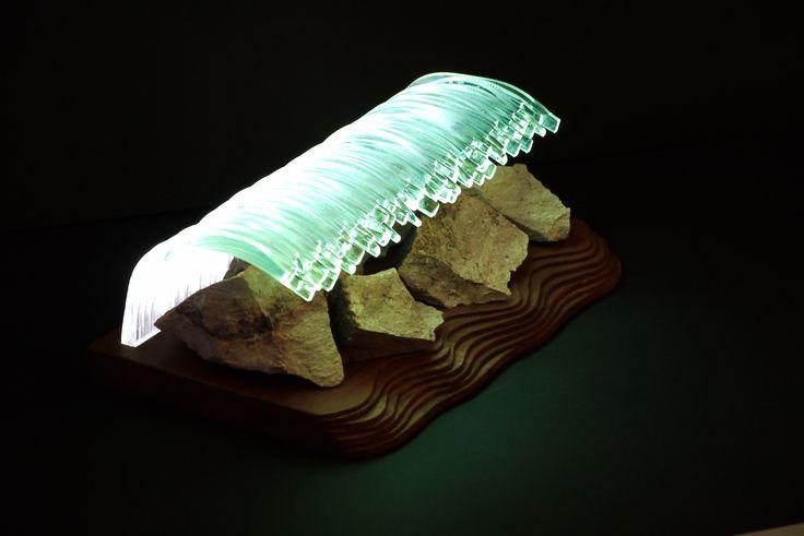 Üvegcsíkokból készült fogazott rogyasztott üvegpanel az alapja ennek a lámpának. A panel vízszintesen került bele a lazúrozott tömbösített bükkfa talpba, és élben kapja a megvilágítást. A vastag rogyasztott üveg fogazott széle vízcseppszerűen csillog, ez adta a tajték ötletét. A látványt a talp szabálytalan megmunkálású széle, illetve az üvegpanel alá helyezett rózsaszínű kövek teszik teljessé.  A lámpa 12cm magas, 35cm széles, súlya 6,4kg (kövekkel). 12voltos, és 220 voltos kivitelben is…