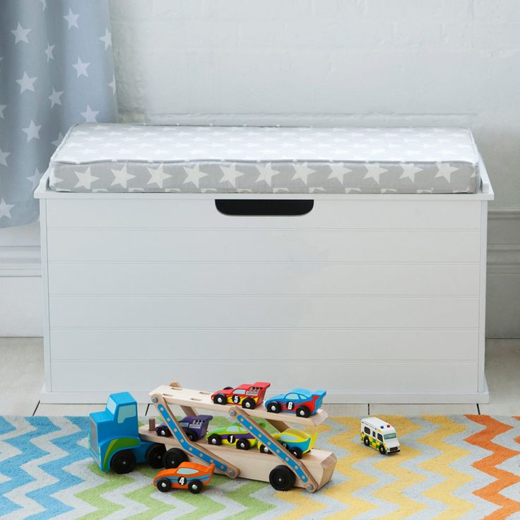 A roomy toy box that doubles up as a seat with a ledge at the back holding the seat cushion in place.