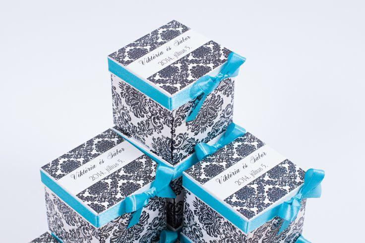 Dobozos esküvői meghívó gyöngy kartonra nyomtatva, fekete mintával, türkiz szatén szalaggal.