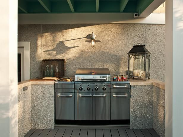 -A stainless steel infrared grill complete with magnetic storage carts carves out a grilling station under the porch overhang. Travertine countertops off the food prep area complement the coquina-style walls, embedded with oyster shell. HGTV Smart Home 2013: Deck Pictures on HGTV