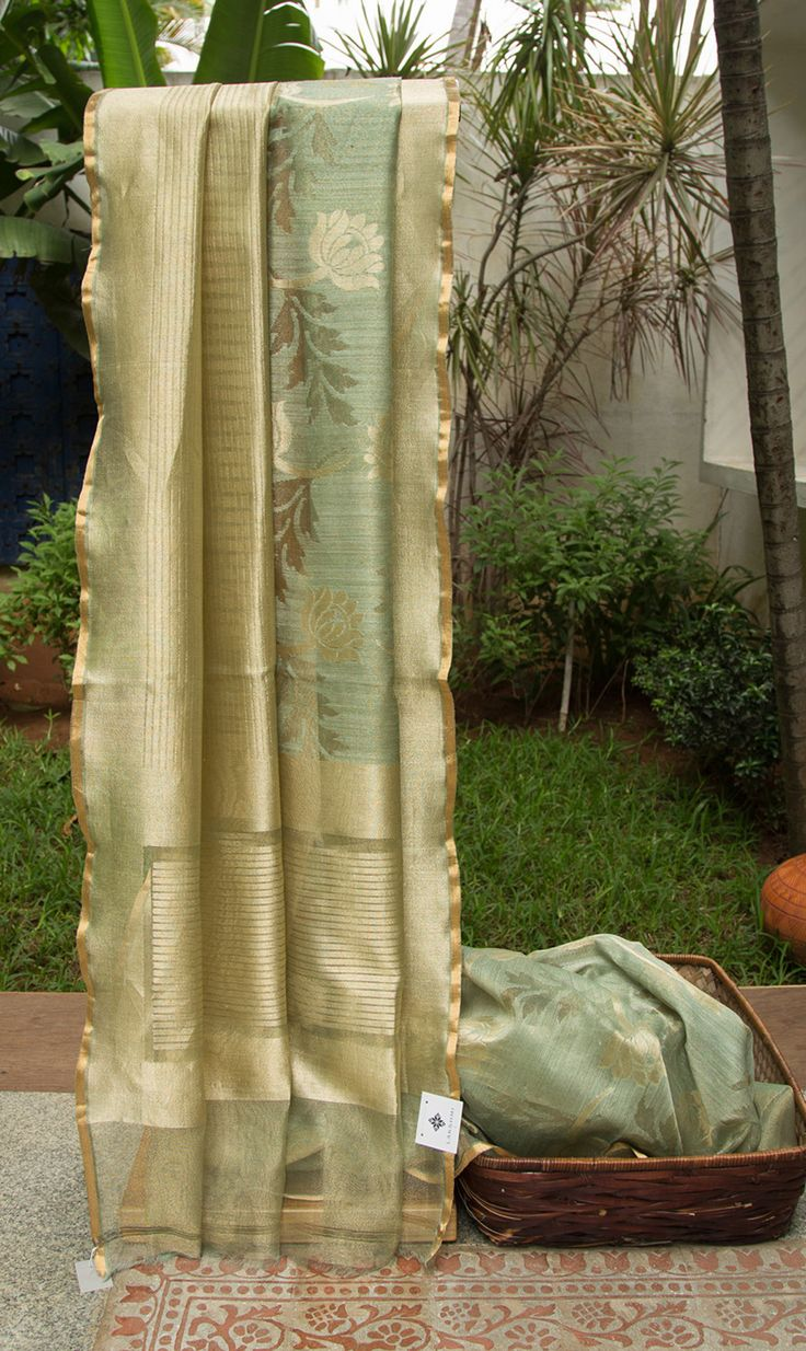 This beautiful Benares net sari is asparagus green and gold colored with a half and half design. One half of the sari has beautiful lotus bhuttas woven over a green base in gold zari. While the ot…