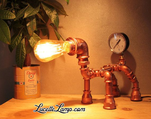 Cette lampe à poser de style industrielle et steampunk est idéale pour une ambiance, usine, atelier ou loft. De qualité artisanale, ce luminaire original et unique a été fabriqué à partir de l'assemblage de raccords de tuyauterie en fonte puis peinte en couleur cuivre.  Dimensions : Hauteur 28 cm, longueur sans ampoule 29 cm, longueur avec ampoule 41 cm, largeur 16 cm. Poids : 2,4 kg Matériaux : Tuyaux de fonte taille 1/2 peints, raccords de plomberie peints. Couleur : Cuivre (autre coul...