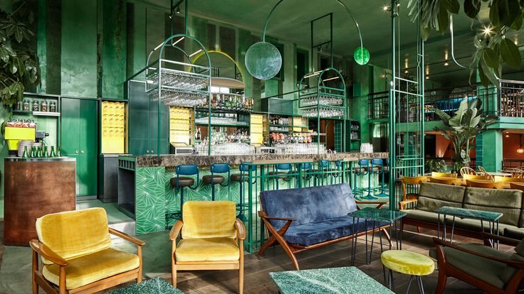 Interior design practice Studio Modijefsky has filled an Amsterdam bar with tropical plants and green surfaces, adding a rainforest-like feel to the venue.