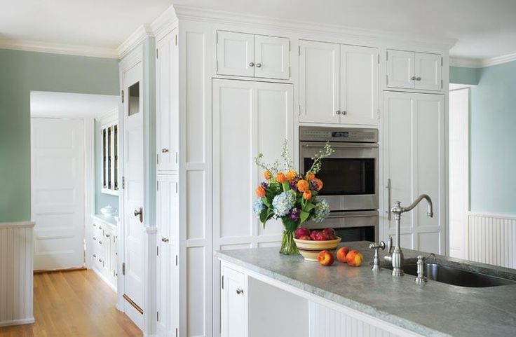 The refrigerator and freezer are hidden behind panels that match the cabinetry..