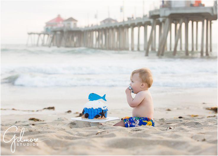 Foster's 1st birthday - Cake Smash Portrait Session - Huntington Beach Photographer, HB, Huntington Beach, Cali, CA, California, beach, ocean, sunset, cake smash, portrait session, first birthday, one year old, adorable, precious, darling, baby swim trunks, baby boy, checkered shirt, pier, HB pier, family, french's bakery, cake, ocean themed cake, blue whale cake, yummy cake, loving the cake, whale and shell frosting, beach cake GilmoreStudios.com
