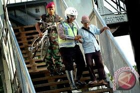 Anggota Korps Marinir bersama anggota Polantas sedang menolong seorang lansia yang akan menyeberang Jembatan Penyebrangan Jl Urip Sumoharjo, Surabaya.  Kemanunggalan antara TNI, POLRI dan masyarakat adalah erat dan tidak terpisahkan.