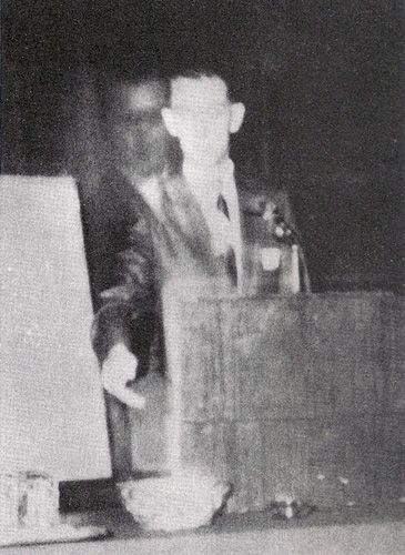 """In 1968, the brother of Robert A.  Ferguson appeared beside him during  a speech at a Spiritualist convention.    """"Walter"""" was killed during World War II.    What is fascinating about this  photograph is that it is a Polaroid and  incapable of being a double-exposure.   And if it were a double-exposure, the  difference in contrast would not be  evident."""