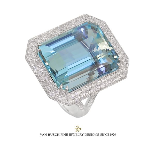 Emerald-cut aquamarine weighing 24.00 ct., surrounded by double row of round brilliant diamonds, 1.16 total ct. weight. Composed of V- shape shoulders with diamonds. Shown in 18k white gold.