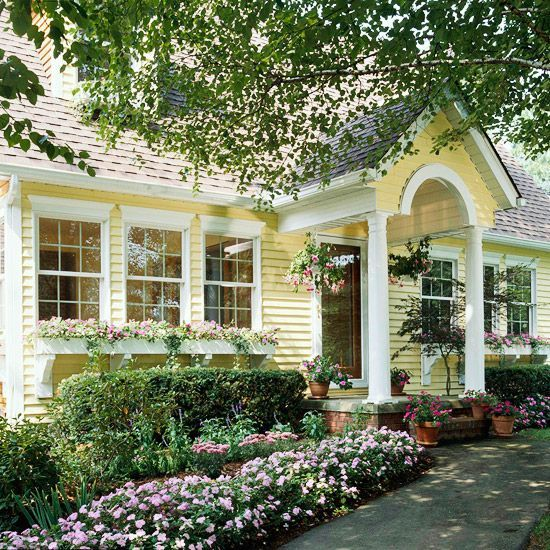 Beautiful blooms and cheery yellow siding accent this cottage home. More ways to add curb appeal: http://www.bhg.com/home-improvement/exteriors/curb-appeal/ways-to-add-curb-appeal/#page=1: Yellow Cottages, Color, Exterior Shutters, White Trim, Flowers Boxes, Curb Appeal, Yellow Houses, Porches, Window Boxes
