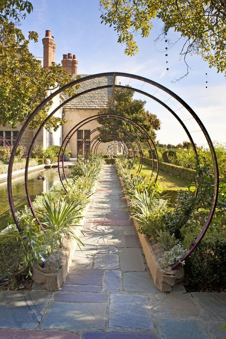 Who could resist walking beneath this? I love the shape of this framework - and that it is echoed on the other side of the pool.  Like a Moon Gate plus it will look wonderful covered with whatever is planted beneath it.