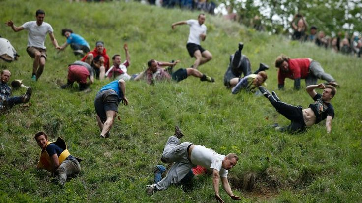 Competitors tumble down Coopers Hill in pursuit of a round Double Gloucester cheese during the 2016 cheese rolling competition near the village of Brockworth, Gloucester.  Adrian Dennis/AFP/Getty Images
