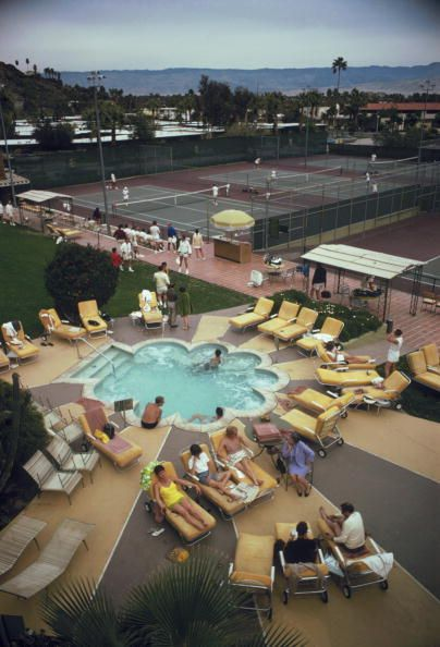 Title:Relaxing At The Club   Caption:Members sunbathe around the pool at Palm Springs Tennis Club, California, circa 1970.       Artist:Slim Aarons  Date:1970