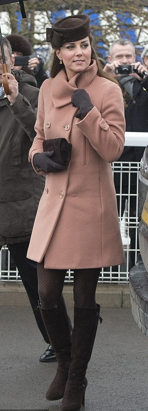 Catherine, Duchess of Cambridge wears a pretty dusky pink wool coat by Joseph paired with a bow-trimmed felt hat by heritage British brand Lock & Co and chocolate-toned tights for the final day of Cheltenham Festival Racecourse