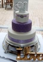 3 tier ivory and lavender wedding cake with heart shape swans as toppers.JPG