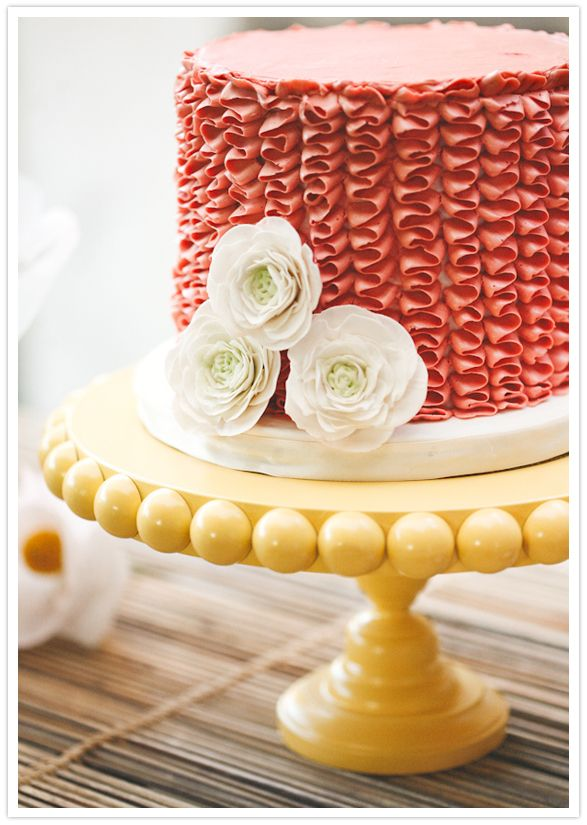 Coral ruffle cake on yellow cake stand.