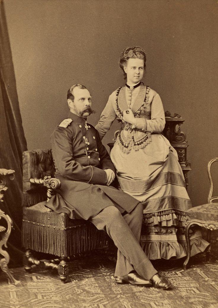 Alexander II, Imperador da Rússia (1818-1881) e Grã-duquesa Maria Alexandrovna (1853-1920) em 1873. Alexander II está sentado de frente parcialmente virado para a direita, vestindo um casaco longo de militar. Grã-duquesa Maria está ao lado dele para a direita, o braço direito apoiado no encosto da cadeira de seu pai e sua mão esquerda levantada contra o peito. Há uma série de itens de mobiliário em torno deles e um tapete modelado no chão.