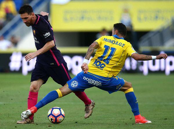 Lionel Messi of Barcelona looks to get past Las Palmas Momo during the La Liga match between UD Las Palmas and Barcelona at Estadio de Gran Canaria on May 14, 2017 in Las Palmas, Spain.
