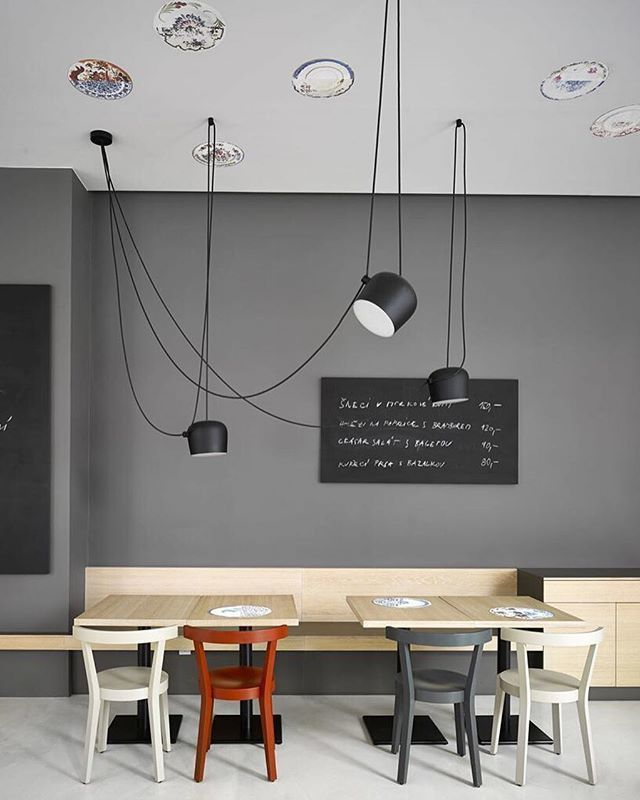 Black AIM pendant lights by Ronan and Erwan Bouroullec add contemporary flavor to this minimalist dining area with wood tables and gray walls.