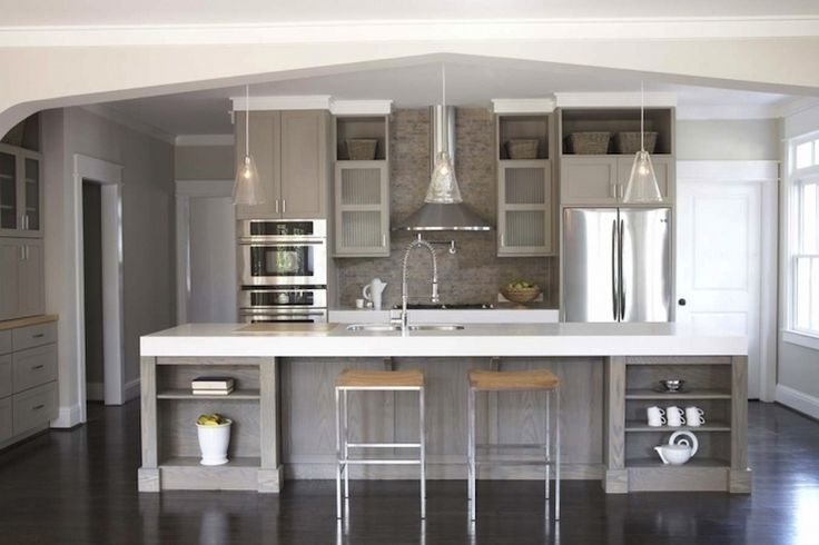 Gorgeous contemporary gray kitchen with gray walls paint color, weather oak kitchen island, taupe gray shaker kitchen cabinets, white quartz countertops, sink in kitchen island, tumbled stone tiles backsplash, tapered glass pendants and modern counter stools.
