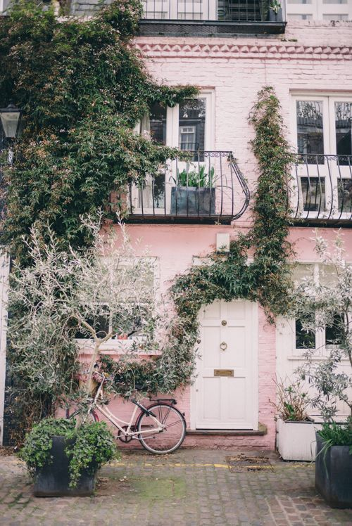 Beautiful pastle pink house with ivy crawling up it. Pink bike