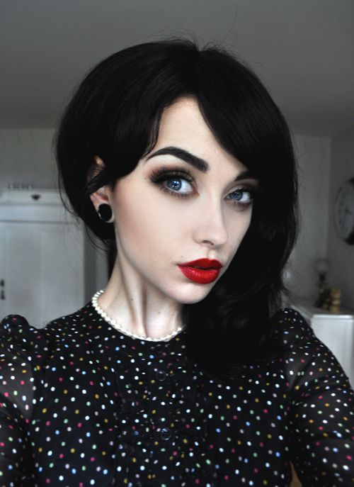 absolutely gorgeous retro/pinup goth look ~ jet black soft curled hair, porcelain skin, defined brows above smoky eyes and candy apple red lips.