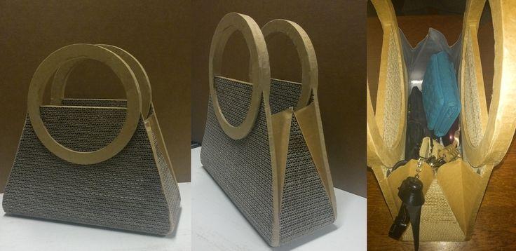 BRIGITTE: borsetta in cartone.  Il tessuto in cartone è ricavato dall'unione di strisce di cartone ondulato tagliate a 6mm di spessore, poi levigate per pareggiarne la superficie. L'interno è rivestito con una carta impermeabile accoppiata ad alluminio. Con la stessa sono stati fatti i soffietti laterali. Tale processo rende flessibili le pareti e permette un'ottimale apertura per accedere agli oggetti contenuti.